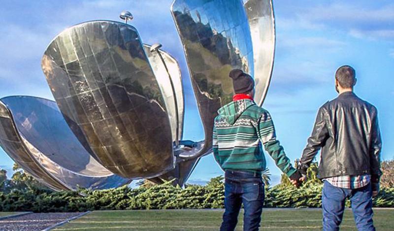 Una pareja junto a la imponente escultura metálica 'Floralis Genérica' en la Plaza de las Naciones Unidas de Buenos Aires.